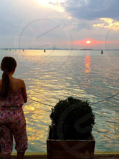 woman wearing floral tank top and pants near flowerbed and water facing the sun during twilight photo
