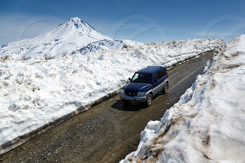 VILYUCHINSKY VOLCANO KAMCHATKA PENINSULA RUSSIA - JUNE 18 2017: Japanese off-road car Mitsubishi Pajero iO driving on mountain road in snow tunnel on background of volcano. photo
