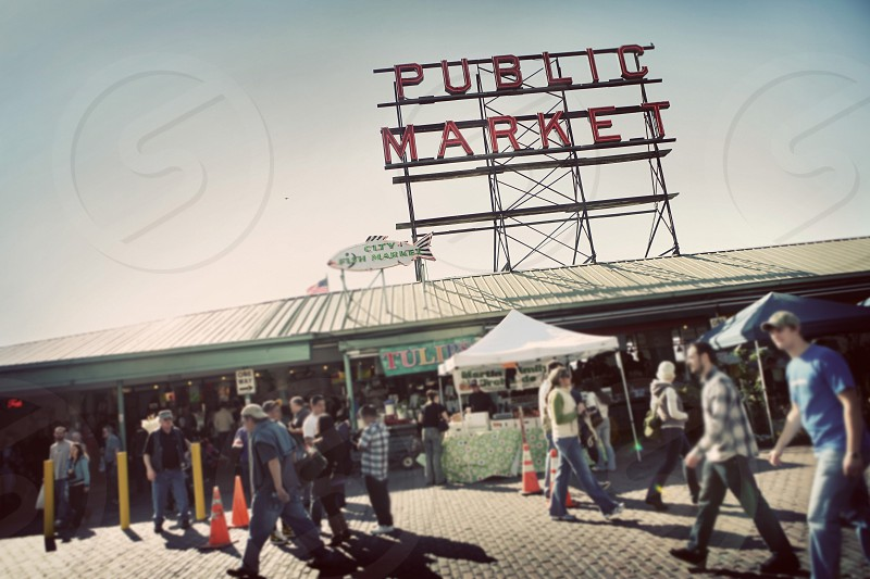 People walking through Pike Place Public Market in Seattle Washington. Tourists cones tents fish pedestrians. photo