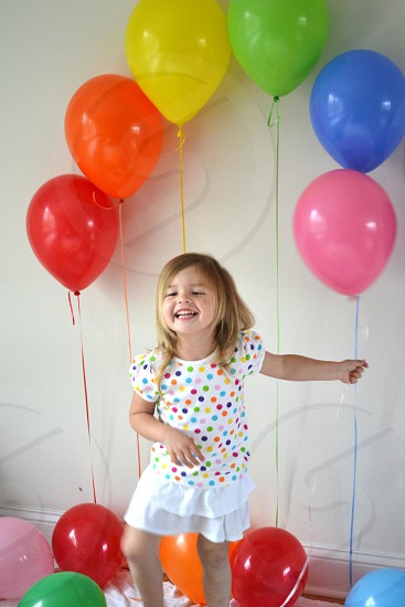 girl smiling holding pink balloon photo