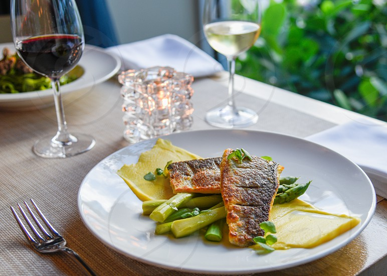 fried fish fillet with green asparagus and yellow sauce dish on ceramic plate photo