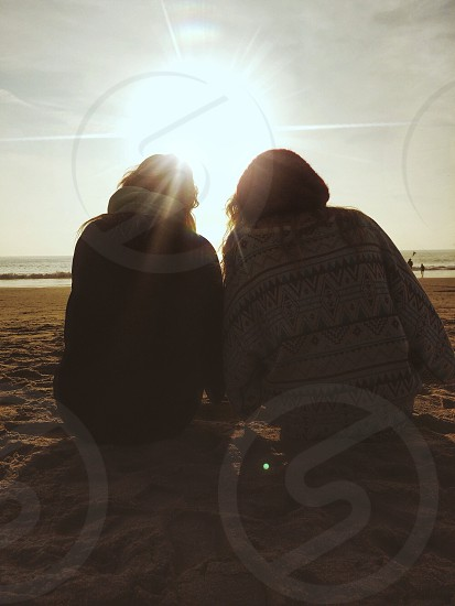two people in sweaters on beach at sunset photo