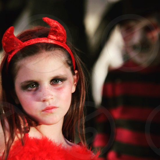 selective photography of girl wearing devil costume photo