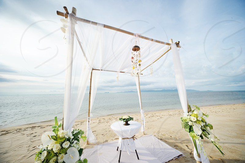 beach wedding altar with white fabric and bouquets photo