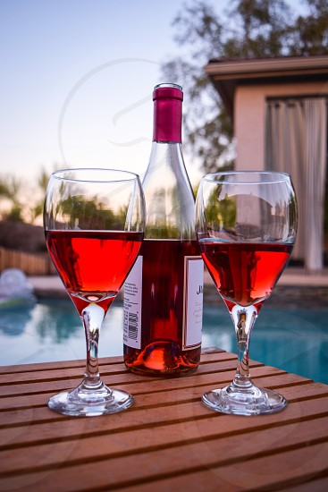 Rose wine wine glasses wine bottle pool summer relaxing swim outdoors photo