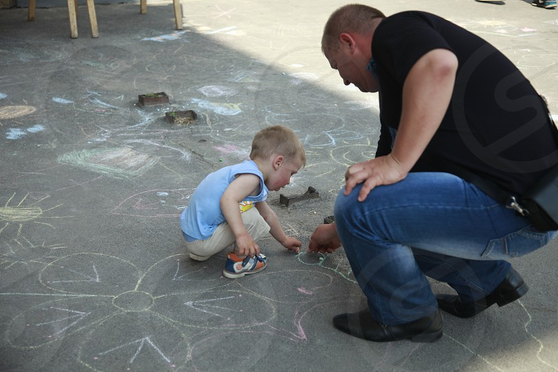 man wearing black shirt writing on the floor with chalk beside toddler wearing blue sleeveless shirt photo
