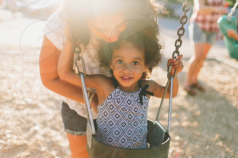 A mother helping her little girl into the swings at golden hour.  photo