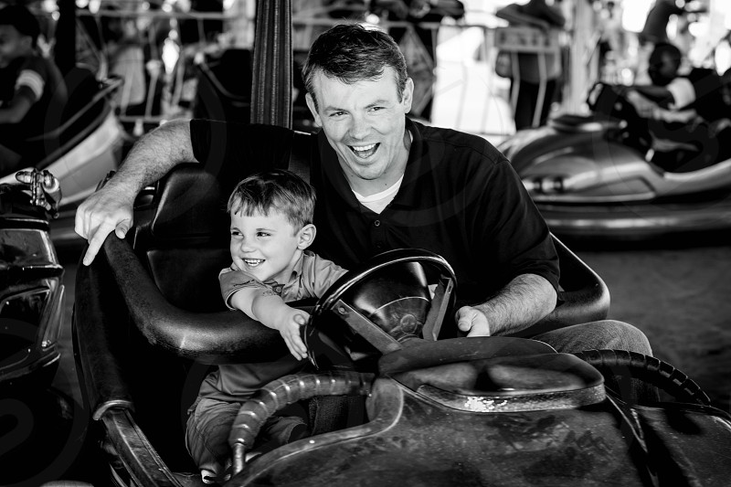 Dad playing with son in a bumper car ride photo