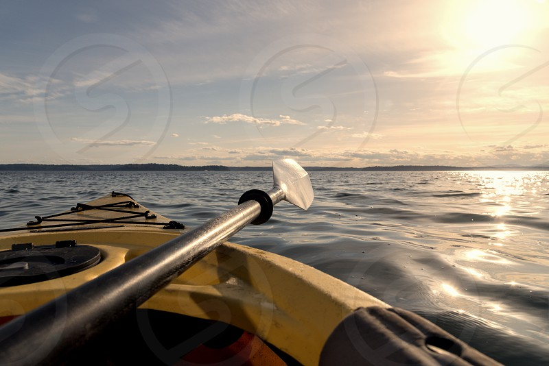 Point of view kayak on water in late afternoon with paddle. photo