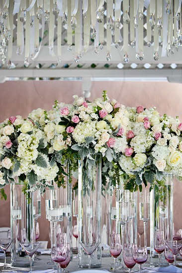 Tall white yellow pink blush flower bouquet centerpiece tablescape glassware crystal floating candles pendants ribbons pendants lattice. photo