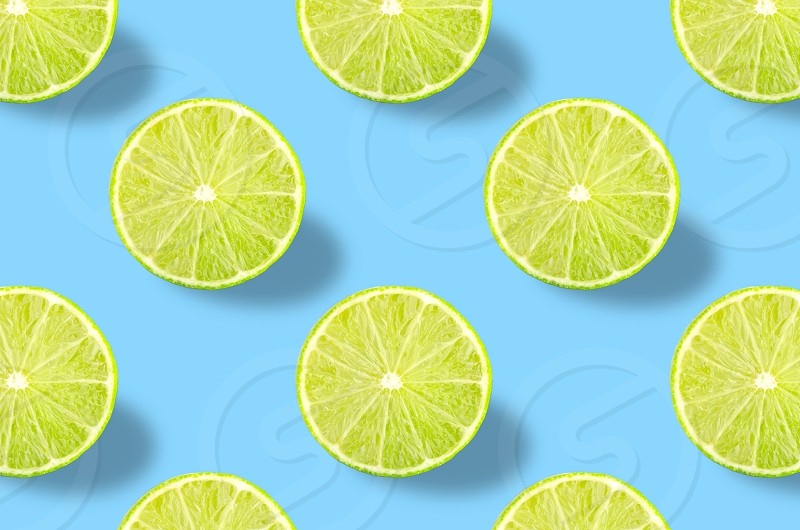 Flat lay fruit pattern of fresh lime slices on blue background. Minimal summer fruits pattern for blog or recipe book photo