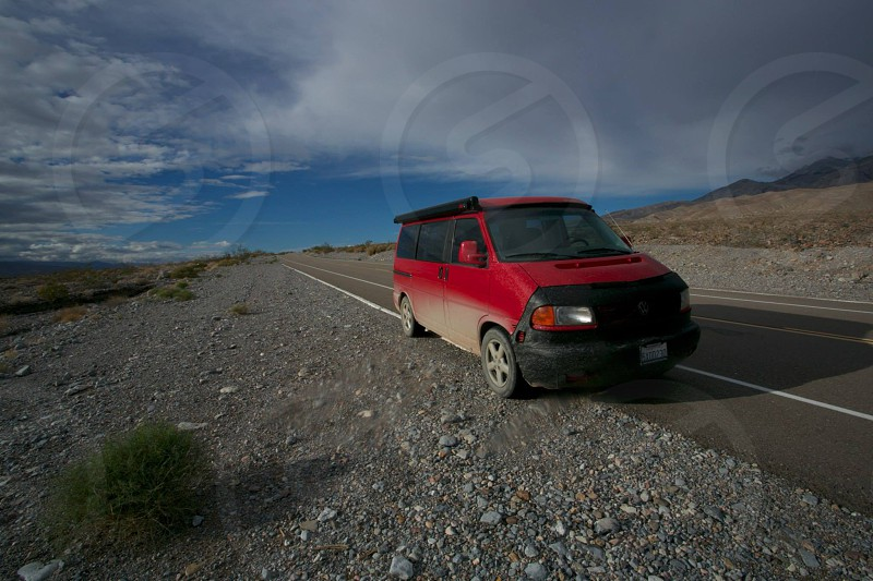 red van parked at roadside near green plants and gray stones during daytime photo