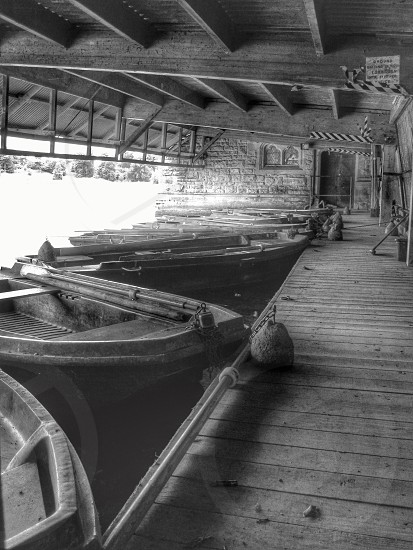 grayscale photo of boats on water beside wooden dock during daytime photo
