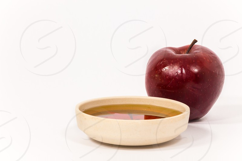 Red apple and bowl of honey isolated on a white background. Symbols of Jewish New Year - Rosh Hashanah. photo