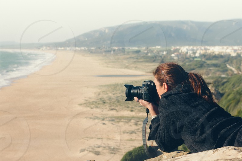 Female Photographer Talking Beautiful Ocean Scene. Female Photographer Lying on her Stomach at the Cliff While Talking Beautiful Ocean Scene Early in the Morning. photo
