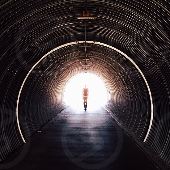 silhouette of standing person at the end of the tunnel photo