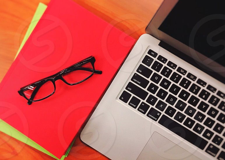 MacBook Pro beside black framed eyeglasses photo