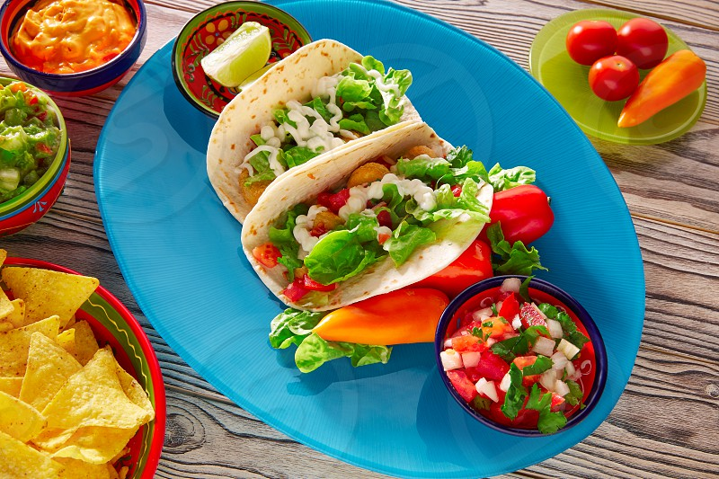 Fish tacos mexican food with guacamole nachos and chili pepper sauce photo