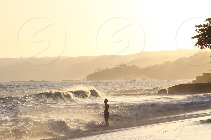 person standing on the beach facing incoming waves photo
