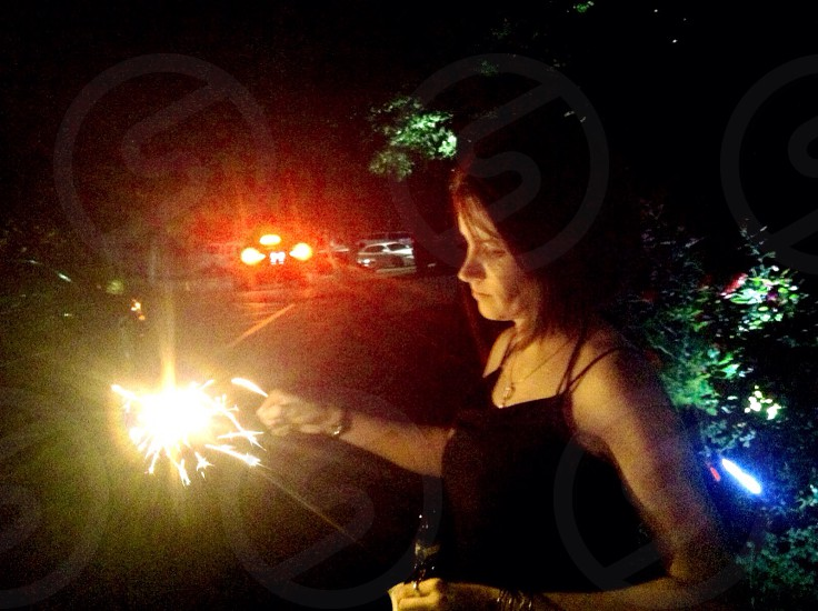 woman in black tank top holding sparklers photo