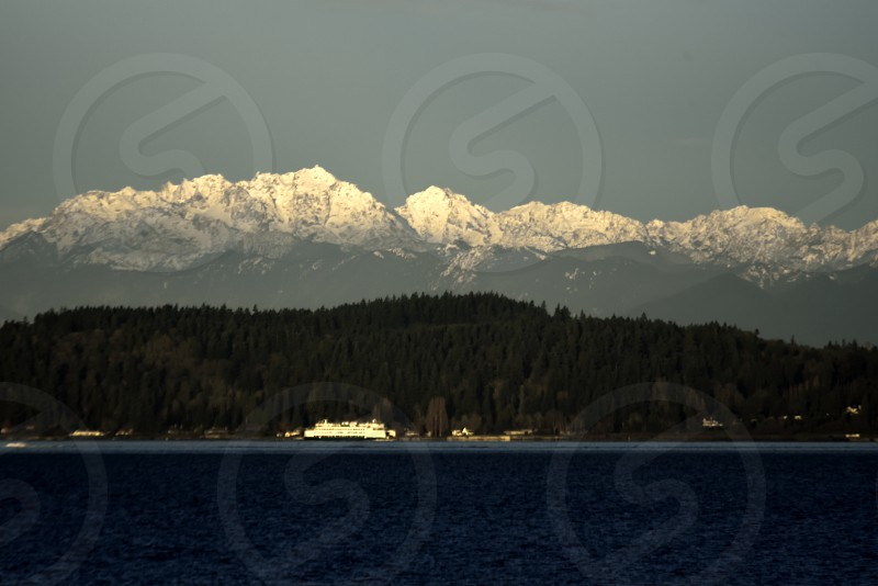 How glorious a greeting the sun gives the mountains!. Morning Olympic Mountains Puget Sound Ferry Crossing Commute snow capped light pine forest rainforest photo