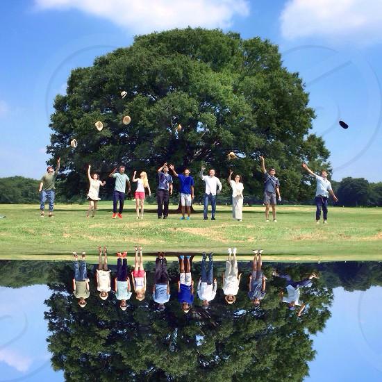 people standing behind green oak tree photo