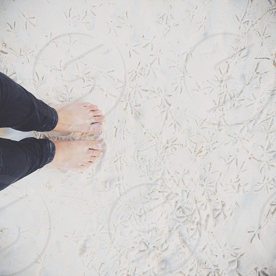 person wearing black denim jeans standing on white sand photo