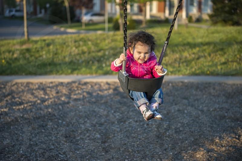 Little girl swinging in neighbourhood park set on background of neighborhood houses. photo
