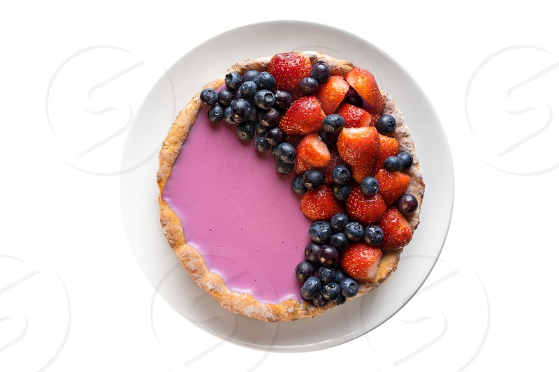 Homemade baked berry pie cake with strawberry and blueberry on white plate on white background flat lay top view photo