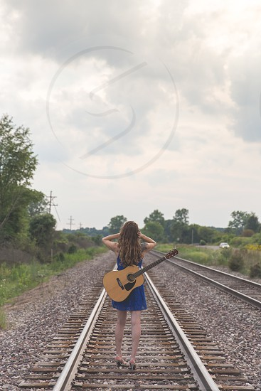 A woman walking away down railroad tracks with her guitar on her back.  Release available upon request.  Also available in non-matte style. photo