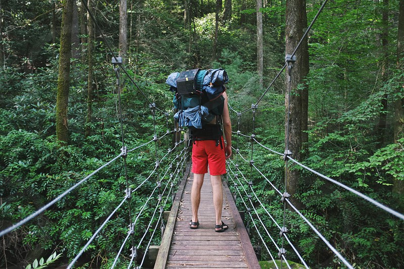 person in red shorts carrying camping bag walking on hanging bridge photo