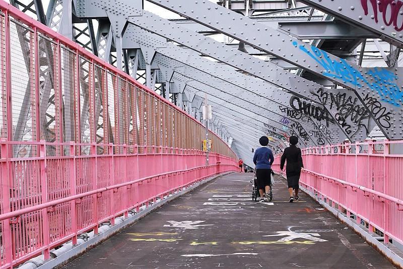 2 people walking though pink metal framed bridge photo