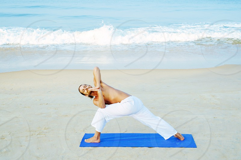 Long hair athletic man with no shirt doing yoga on blue mat at the beach. Revolved side angle pose yoga photo