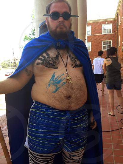 man in with blue cape  with and hand print on chest photo