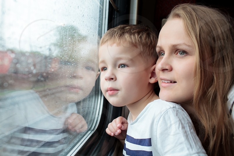 Mother and son looking through a train window as they enjoy a days travel with the small boys face reflected in the glass photo