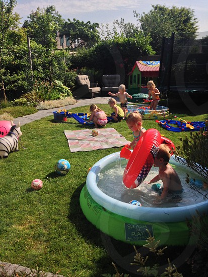 children wearing swimwear playing with 2 inflatable pools and inflatable floaters outside during daytime photo