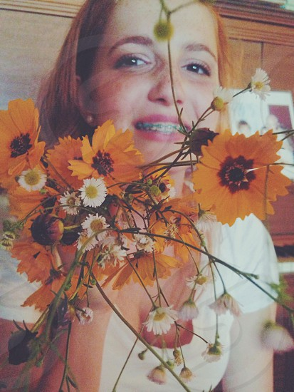 view of woman holding yellow petal flower photo
