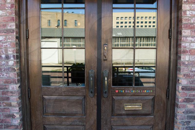 brown wooden half glass door beside concrete wall bricks photo