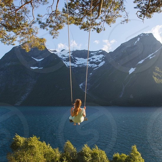 A girl swings out over the fjord.  photo