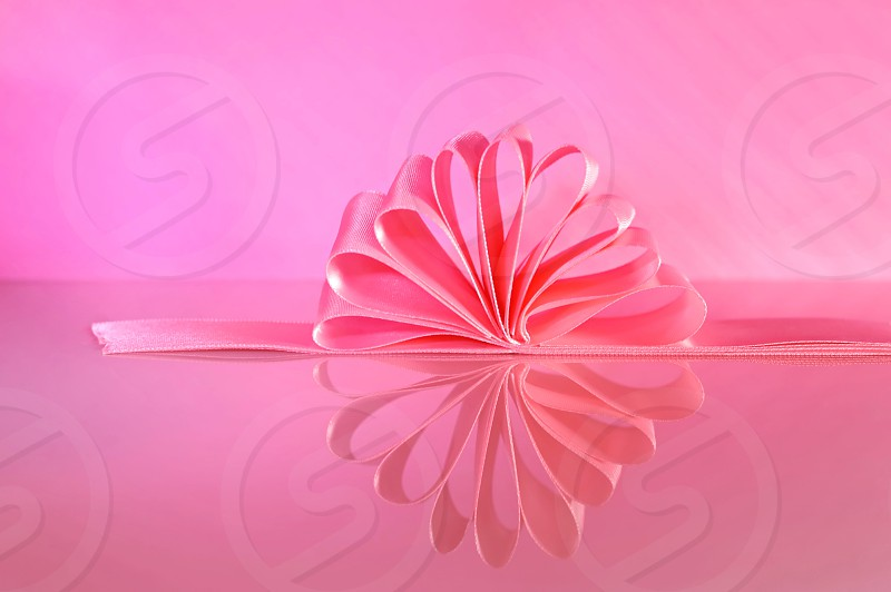 Pink ribbon and reflection against a pink background. photo