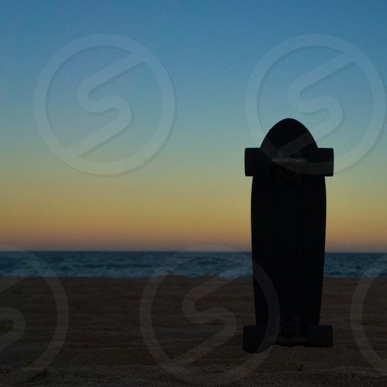 silhouette photography of surfboard on the seashore photo