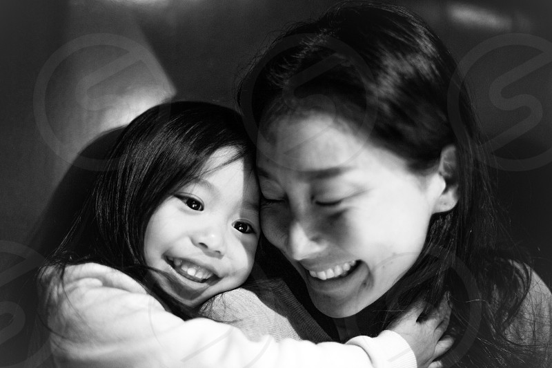 woman in grey shirt smiling with a girl in white long sleeved shirt photo
