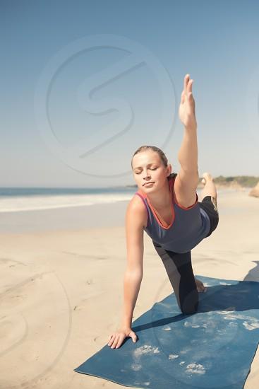 Caucasian woman exercising yoga at a beach eyes closed. photo