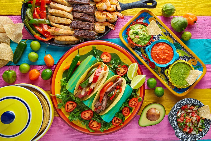 Mexican chicken and beef fajitas tacos in colorful table with sauce photo