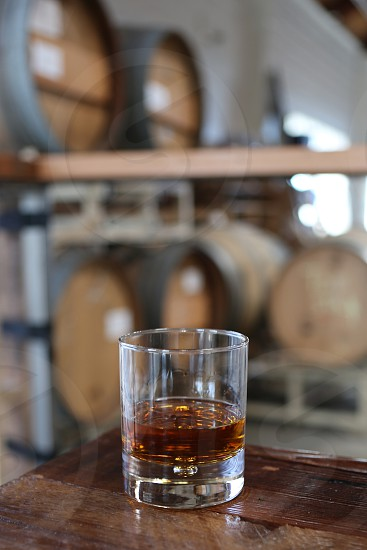 Whiskey in glass with barrels in the background photo