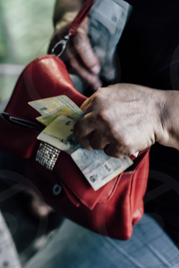 person carrying red leather sling bag holding banknote photo