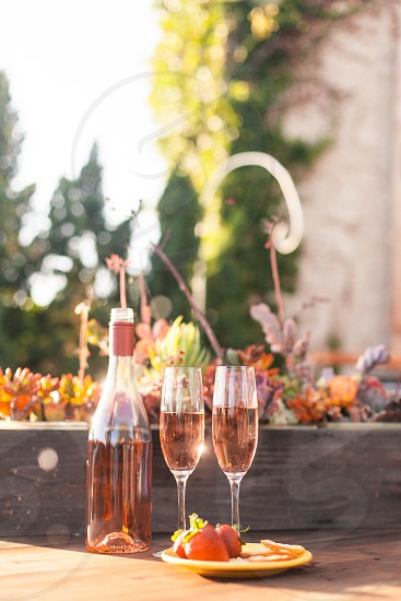 two champagne glass served half full beside a champagne bottle and in front of it is a served strawberry fruit placed on a saucer photo