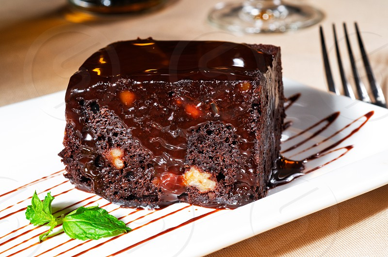 fresh baked delicious chocolate and walnuts cake with mint leaf beside photo