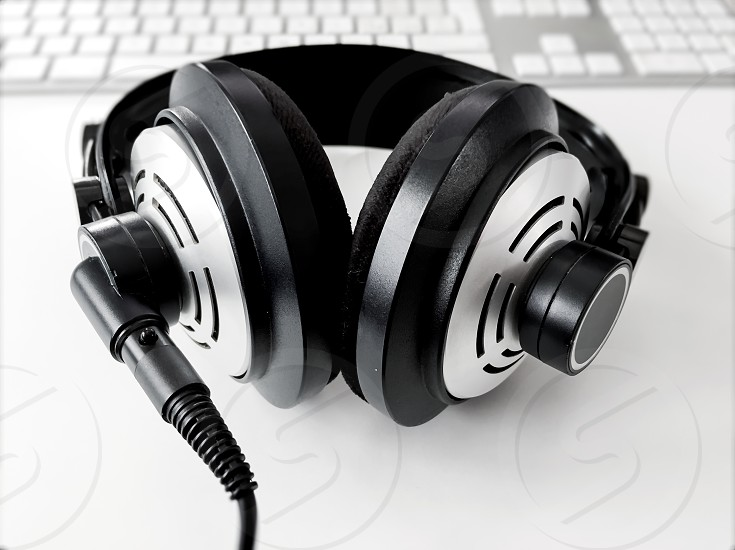 professional headphone in black and white on a white table with a computer keyboard blurred in the background photo