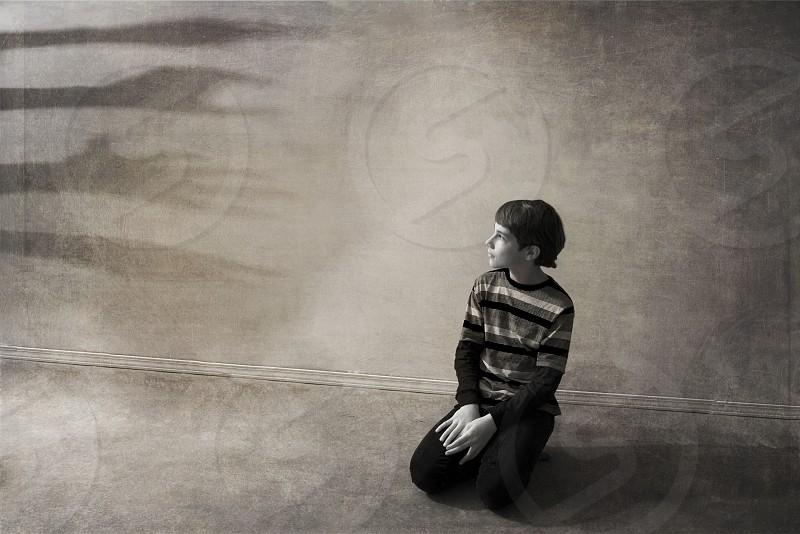 black and white photo of boy kneeling photo